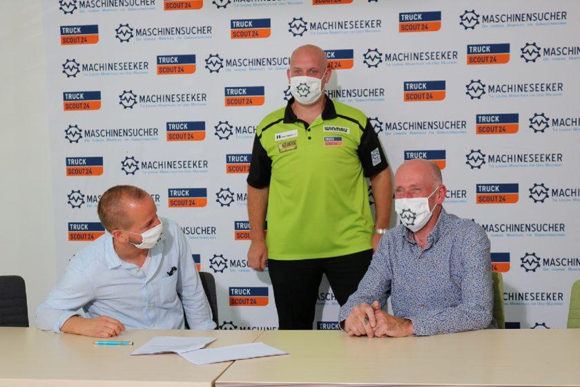Die Geschäftsführung nach der Vertragsunterzeichnung mit Michael van Gerwen im Hintergrund.